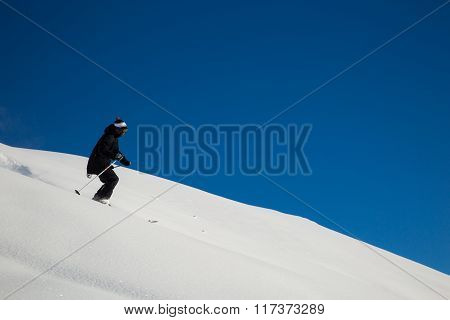 Male Skier Skiing In Fresh Snow On Ski Slope On A Sunny Winter Day At The Ski Resort In Georgia
