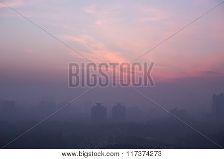 City skyline at sunset, lots of smog and bad ecology.