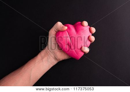 Man's hand squeezing pink heart on a black background