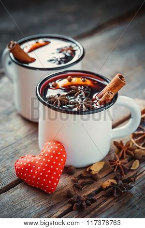 Mulled Wine In Rustic Mugs With Spices And Red Heart