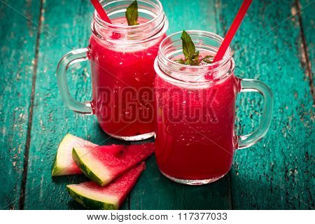 Fresh watermelon smoothie drink in mason jar on black stone.