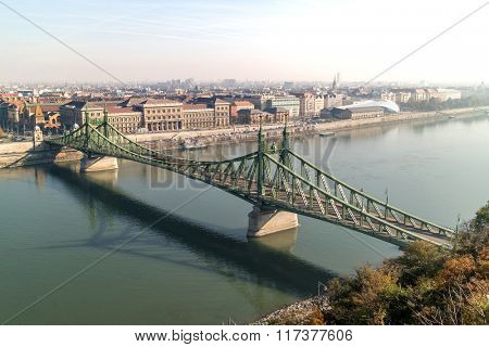 Liberty Bridge of Budapest on a bright autumn day. Side panoramic view with two banks of the river.