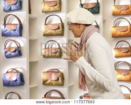Shopping woman chooses lady's handbag in store. Woman looking to lady's handbag or shop window.