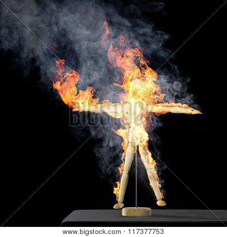 Burning Wooden Doll On Desktop