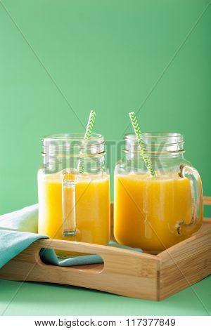 healthy mango pineapple smoothie in mason jars