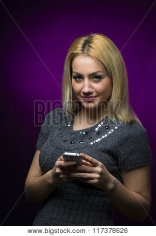 Happy Blonde Haired Model Holding Smartphone On Black Background