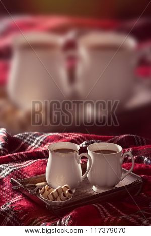 Tray of hot chocolate drinks on tartan rug with same image blurred in the background - useful for advertising concept