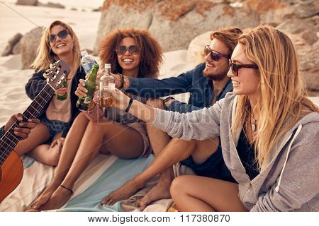 Group Of Friends Cheers With Beers At The Beach