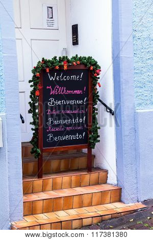The Inscription Welcome 7 Language On A Black Chalkboard Decorated For Christmas On The Steps Of The