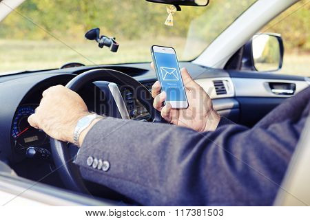 man reading mail on the phone while driving his car