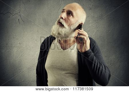 surprised senior man with cellphone over dark wall