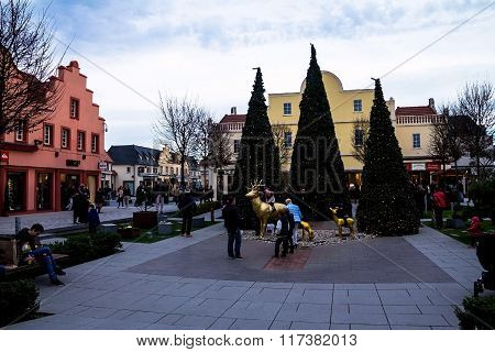 Unidentified visitors at Christmas decorated  square inside country  outlet stores