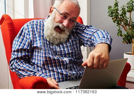 evil senior man screaming and looking at laptop