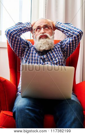 fatigued senior man sitting on the chair with laptop and looking up