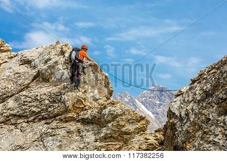Brave man climbs rocky ridge