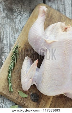 Whole Raw Chicken With Rosemary On A Cutting Board