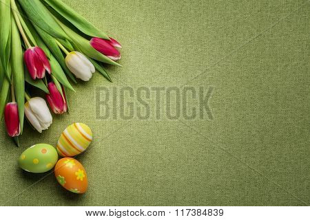 Tulips and easter eggs on green background
