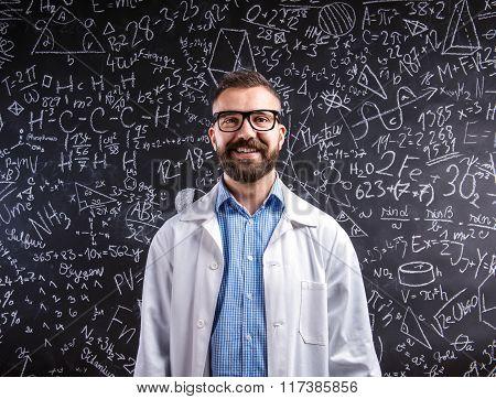 Teacher in white coat  and eyeglasses against big blackboard wit