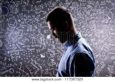 Teacher silhouette against big blackboard with mathematical symb