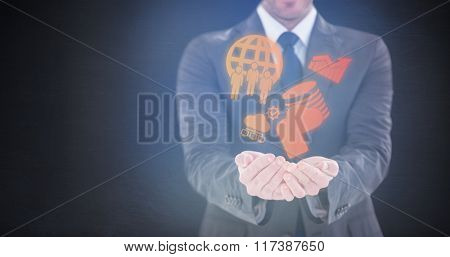 Smiling businessman presenting with hands against dark room