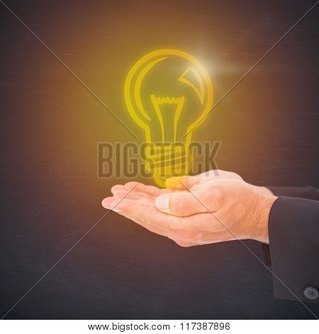 Businessman holding his hands out against black room