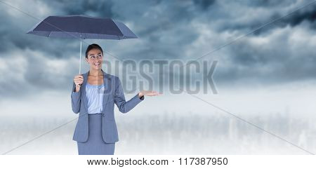 Smiling businesswoman holding umbrella against room with large window looking on city