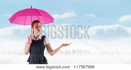 Pretty redhead businesswoman holding umbrella against city on the horizon