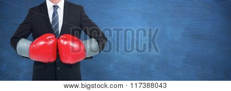 Businessman with boxing gloves against blue chalkboard