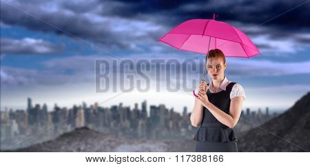 Pretty redhead businesswoman holding umbrella against large city on the horizon
