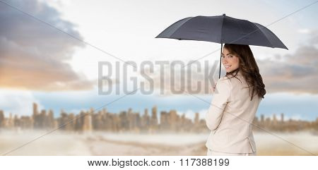 Rear view of classy businesswoman holding umbrella against path in yellow field leading to city