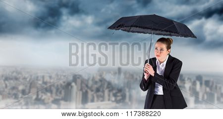 Businesswoman holding a black umbrella against room with large window looking on city