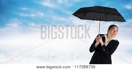 Young businesswoman holding umbrella against dusty path leading to city under the clouds