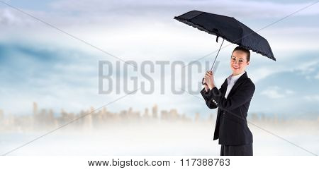 Businesswoman holding a black umbrella against large city on the horizon