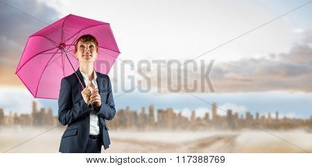 Businesswoman with umbrella against path in yellow field leading to city