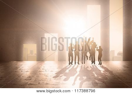 Silhouetters celebrating against cityscape background