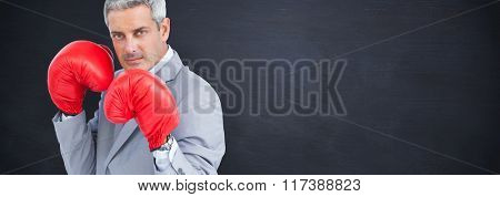 Tough businessman with boxing gloves against blackboard