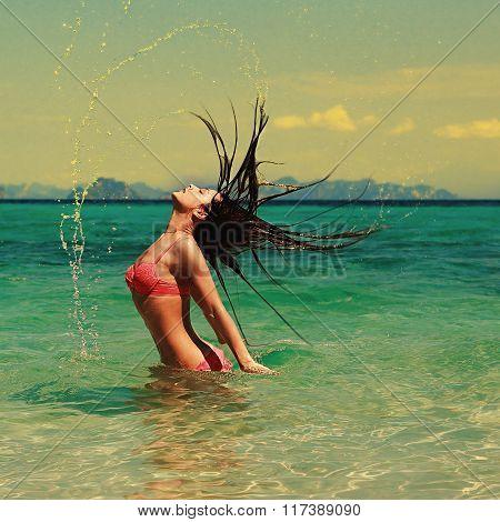 Beautiful Model Woman Splashing Her Hair In Turquoise Azure Water In Pink Bikini