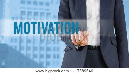 The word motivation and businesswoman pointing against low angle view of city buildings