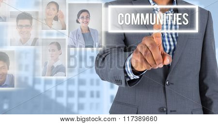 Focused businessman pointing against low angle view of city buildings