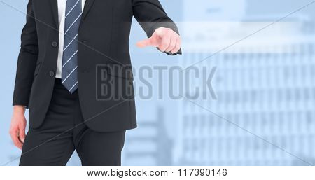 Mid section businessman pointing with his finger against low angle view of city buildings