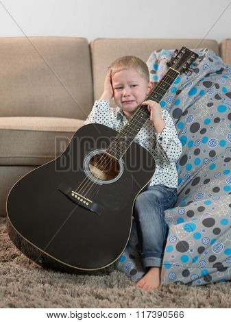 Little boy with a guitar and crying