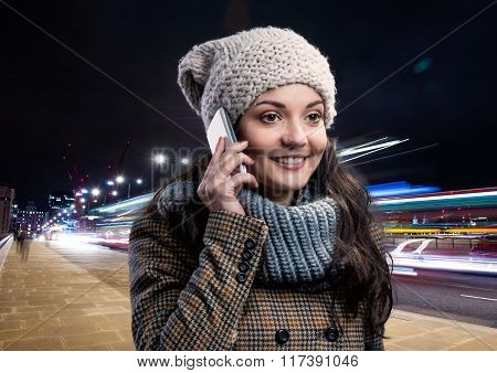 Woman in winter coat with smart phone in night city