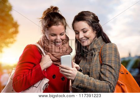 Two women in winter coats with phone in sunny park