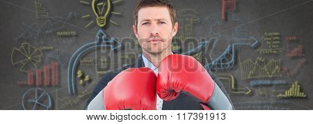 Businessman with boxing gloves against brainstorm in grey room