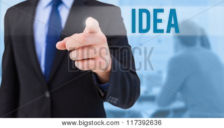 The word idea and businessman pointing his finger at camera against blue background