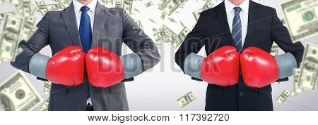 Businessman with boxing gloves against dollars falling