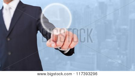 Smiling businessman in suit pointing against view of cityscape