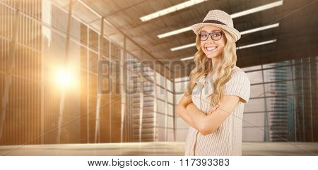 Gorgeous smiling blonde hipster with arms crossed against modern room overlooking city