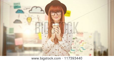 Smiling hipster woman drinking coffee against adhesive notes on window