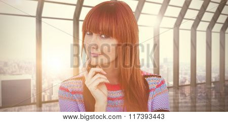 Portrait of a smiling hipster woman against room with large window looking on city